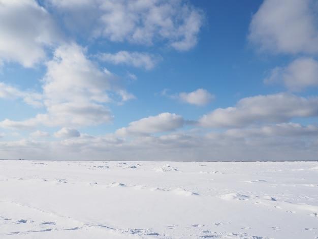 Zamarznięte morze ze śniegiem i chmurami na niebie w słoneczny dzień