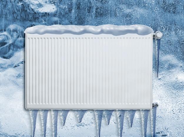 Zamarznięty grzejnik na zewnątrz zimą pokryty śniegiem
