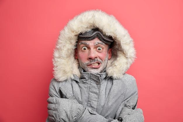 Zamarznięty mężczyzna drży z zimna ma czerwoną twarz zakrytą lodowatą brodą, nosi kurtkę z kapturem, którą trzeba ogrzać podczas zimowej wyprawy.