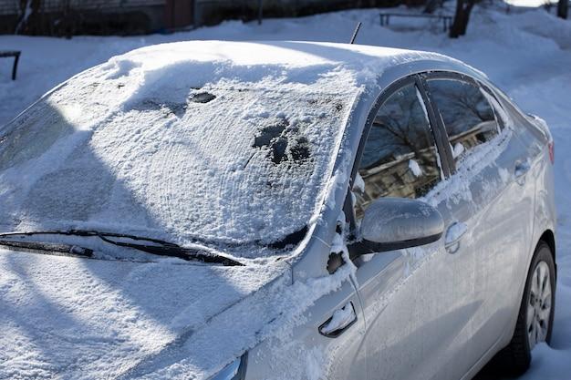 Zamarznięty samochód na ulicy miasta w zimie. zdjęcie wysokiej jakości