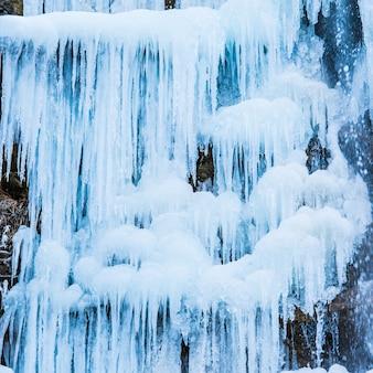 Zamarznięty wodospad niebieskich sopli na skale