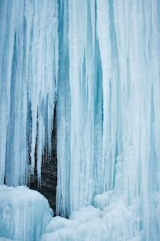Zamarznięty wodospad z lodem w niebiesko-białym kolorze w zimie