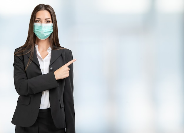 Zamaskowana biznesowa kobieta wskazując palcem na jasną przestrzeń