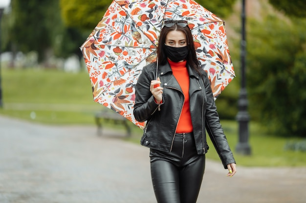 Zamaskowana dziewczyna idzie ulicą. dziewczyna w masce ochronnej spacery po parku z parasolką w deszczu. zakażenie koronawirusem covid-19