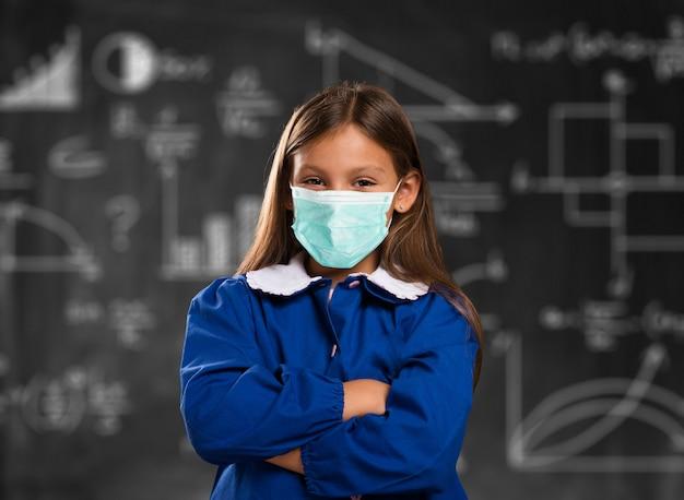 Zamaskowana dziewczyna w szkole przed blackboard