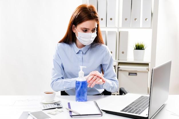 Zamaskowana kobieta biznesu myje ręce żelem w miejscu pracy