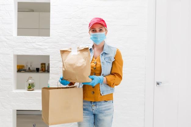 Zamaskowana kobieta dostarczająca jedzenie podczas epidemii wirusa, paniki związanej z koronawirusem i pandemii.