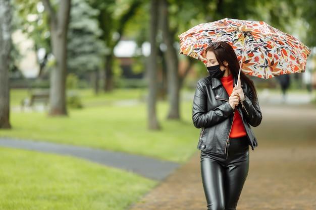 Zamaskowana kobieta idzie ulicą. kobieta w masce ochronnej spacery po parku z parasolką w deszczu. zakażenie koronawirusem covid-19