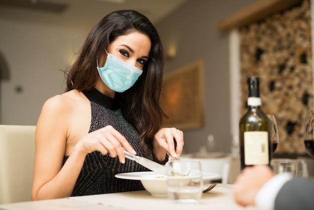 Zamaskowana kobieta jedzenia w restauracji