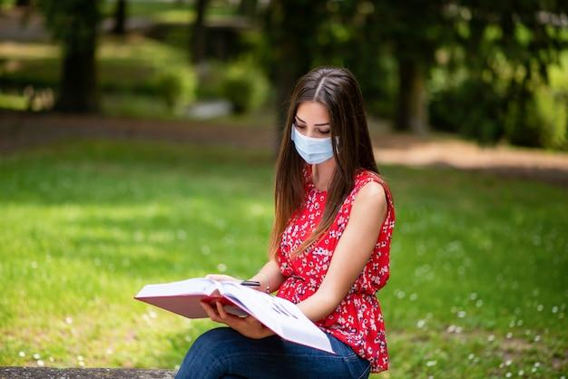 Zamaskowana kobieta siedzi w parku i czyta książkę