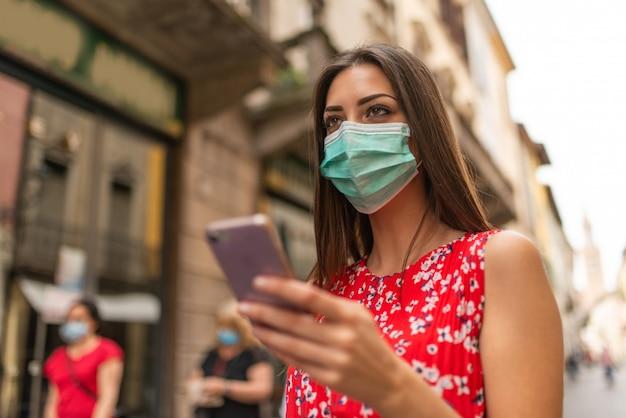 Zamaskowana kobieta spaceru po mieście podczas korzystania z telefonu komórkowego