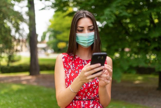 Zamaskowana kobieta używa jej telefon komórkowego