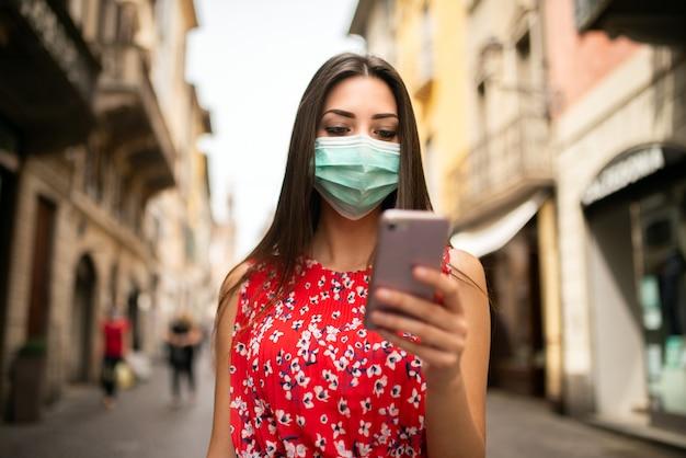 Zamaskowana młoda kobieta spacerująca po mieście podczas korzystania z telefonu komórkowego