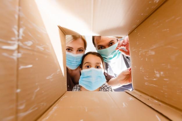 Zamaskowana rodzina zaglądająca do pudełka. bezdotykowa dostawa żywności i towarów podczas kwarantanny koronawirusa dla osób odizolowanych.