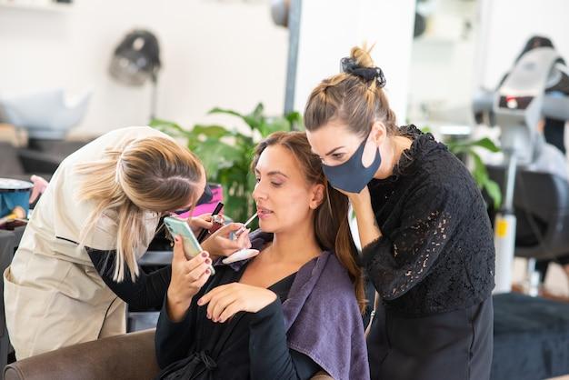 Zamaskowani fryzjerzy pracujący nad włosami i umalowani przez klienta, pracują podczas koronawirusa i koncepcji mody