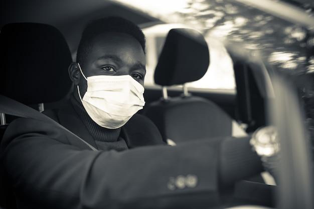 Zamaskowany afrykański biznesmen prowadzący swój samochód podczas pandemii koronawirusa. czarno-biały styl