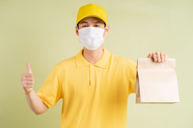 Zamaskowany azjatycki doręczyciel trzymał papierową torbę i trzymał kciuk