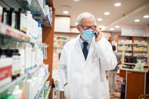 Zamaskowany farmaceuta rozmawiający przez telefon podczas spaceru w swojej aptece, koncepcja koronawirusa