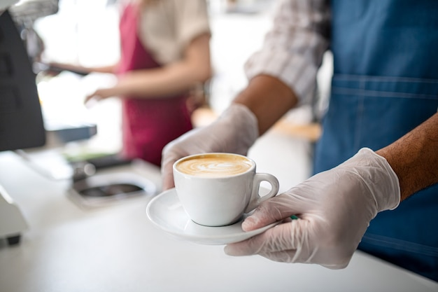 Zamaskowany kelner serwujący kawę w kawiarni koronawirus małej firmy i nowa normalna koncepcja