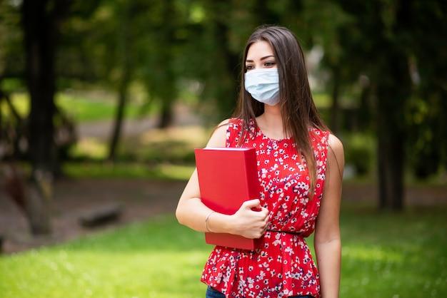 Zamaskowany kobieta uczeń trzyma książkę plenerową