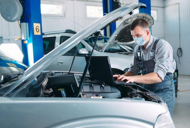 Zamaskowany mechanik sprawdza samochód na stacji obsługi