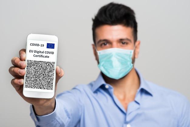 Zamaskowany mężczyzna pokazujący swój europejski certyfikat szczepionki przeciw krowim, zwany także green pass