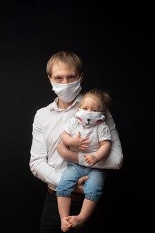 Zamaskowany ojciec trzyma swoją małą córeczkę. koncepcja ochrony koronawirusa.
