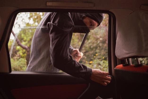 Zamaskowany złodziej odblokowuje i otwiera okno samochodu, aby ukraść mienie