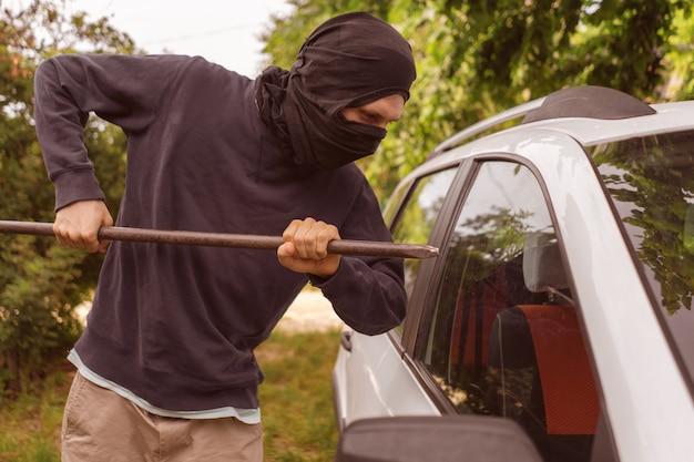 Zamaskowany złodziej stojący przy samochodzie i próbujący wybić okno kowbarem