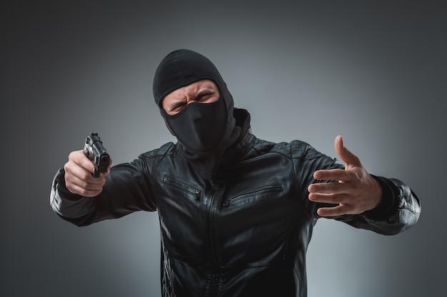 Zamaskowany złodziej z pistoletem, patrząc w kamerę.