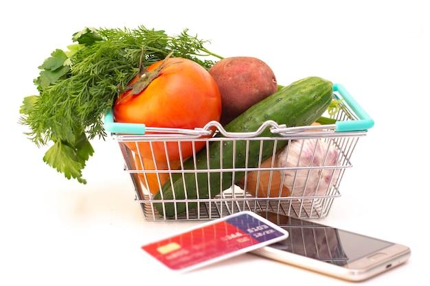 Zamawianie jedzenia w domu w związku z izolacją od koronawirusa. telefon i karta. pomidor, ogórek, warzywa w koszu.