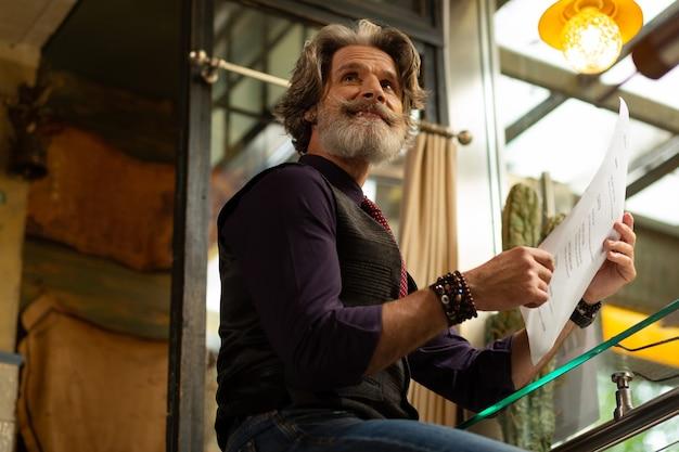 Zamawianie kawy. uśmiechnięty brodaty mężczyzna z menu w ręku jest gotowy do złożenia zamówienia w kawiarni.