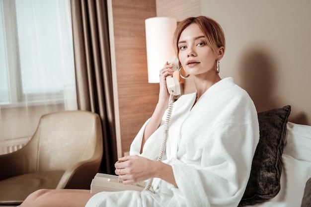 Zamawianie śniadania. szczupła kobieta ubrana w biały szlafrok dzwoniąc do obsługi pokoju zamawiając śniadanie