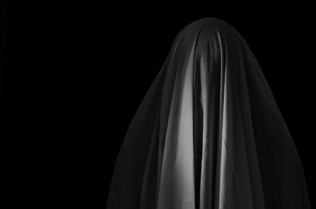 Zamazana fotografia biały ducha prześcieradło na czerni.