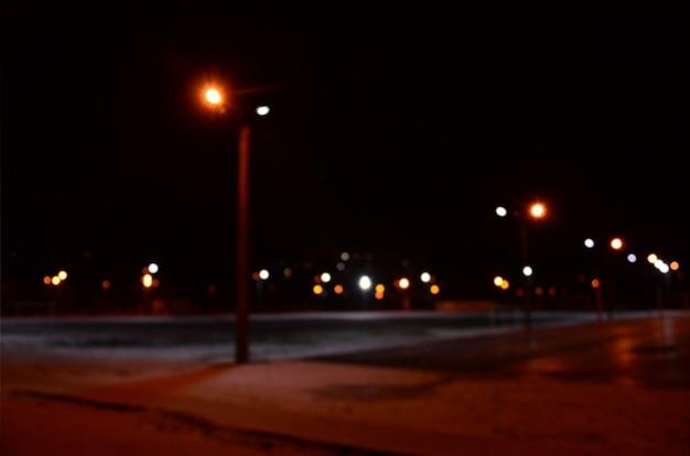 Zamazana fotografia szkolny boisko przy nocą z jaskrawymi światłami