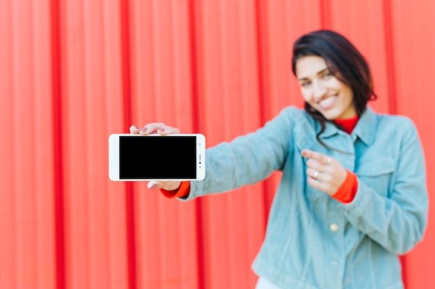 Zamazana kobieta wskazuje w kierunku pustego ekranu telefonu komórkowego