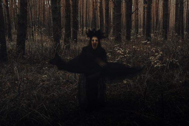 Zamazana przerażająca czarna sylwetka złej wiedźmy w ciemnym lesie