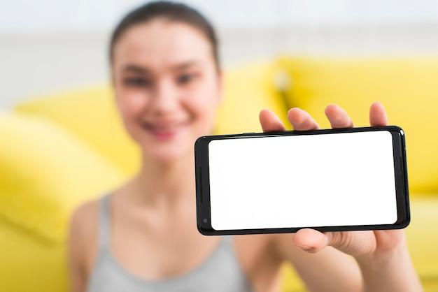 Zamazana sprawności fizycznej dziewczyna pokazuje telefon komórkowego