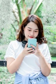 Zamazane obrazy miękkie azjatyckiej ładnej kobiety w wieku 20 lat, korzystającej z telefonu komórkowego