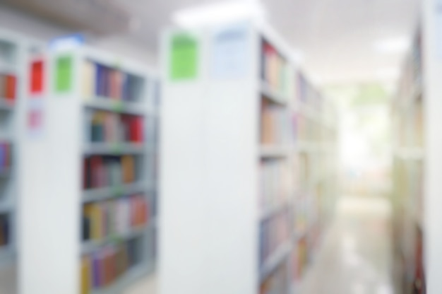 Zamazane wnętrze biblioteki publicznej z książkami na drewnianych półkach. dzień edukacji i książki.