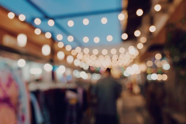 Zamazani noc rynku festiwalu ludzie chodzi na drodze