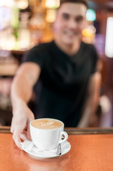 Zamazany barista daje kawie