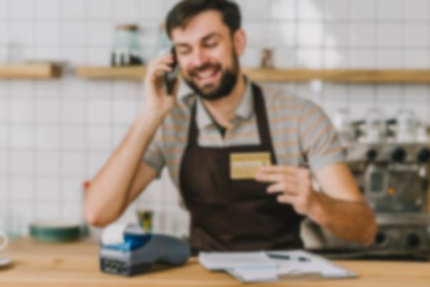 Zamazany barista z kredytową kartą mówi na smartphone