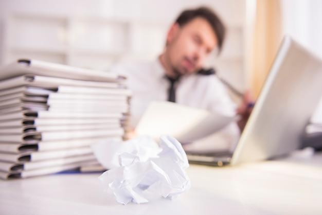 Zamazany biznesmen pracuje przy biurem