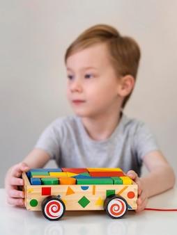 Zamazany chłopiec bawić się z drewnianym samochodem