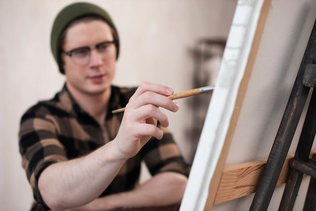 Zamazany mężczyzna artysta maluje na płótnie