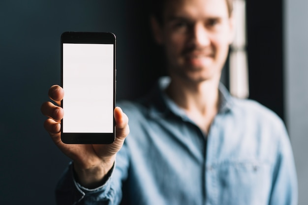 Zamazany młody człowiek pokazuje smartphone z pustym bielu ekranem