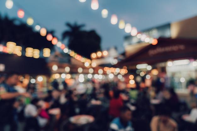 Zamazany noc targowego festiwalu ludzie chodzi na drodze.