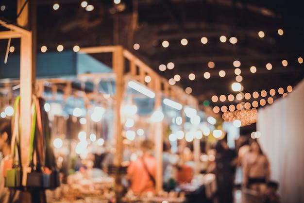 Zamazany noc targowego festiwalu ludzie chodzi na drodze