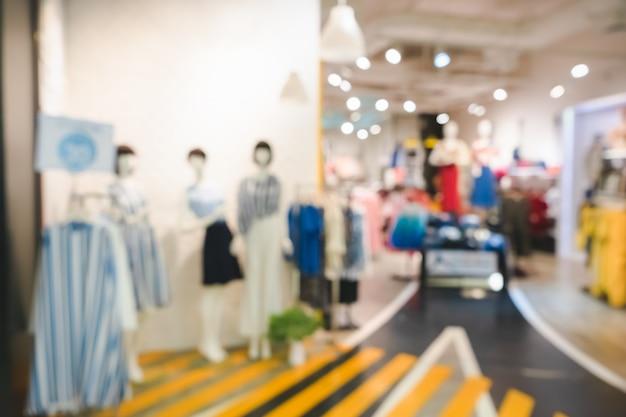 Zamazany obraz butikowego wyświetlacza z manekinami w modnych sukienkach na tle
